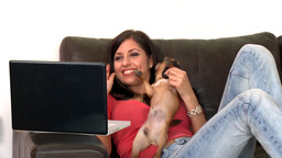 Laughing woman and her dog using a laptop Footage
