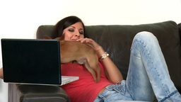 Pretty woman and her dog using a laptop Footage