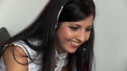Portrait of a smiling woman talking with headset o Stock Video Footage