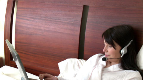 Young woman using a laptop with headset on Stock Video Footage