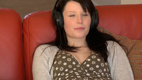 Relaxed woman listening music sitting on sofa Footage