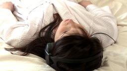 Pensive woman listening music lying on bed Footage