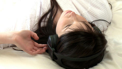 Charming woman listening music lying on bed Footage
