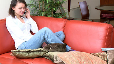 Laughing woman talking on phone sitting on sofa Footage