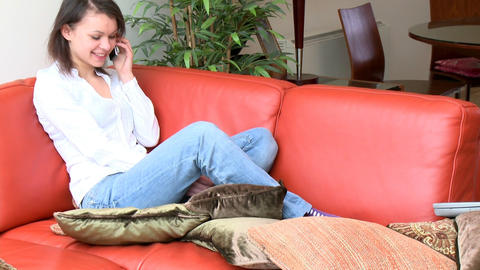 Jolly woman talking on phone sitting on sofa Footage