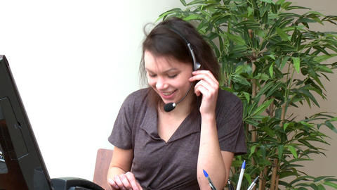 Smiling woman with headset on working at a compute Stock Video Footage