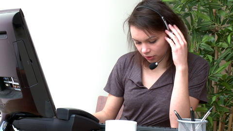 Concentrated woman with headset on working at a co Footage