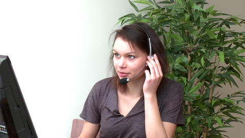 Jolly woman with headset on working at a computer Footage