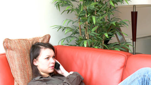 Relaxed woman talking on phone sitting on sofa Footage