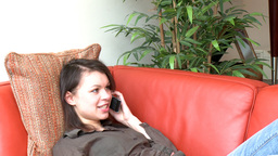 Pensive woman talking on phone sitting on sofa Footage