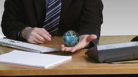 Businessman with a rotary terrestrial globe in his Stock Video Footage