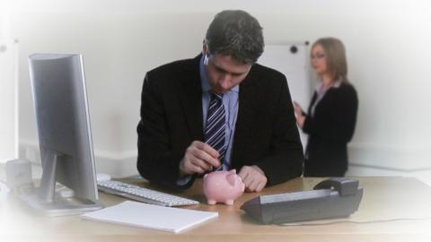 Businessman putting money in his piggybank Footage