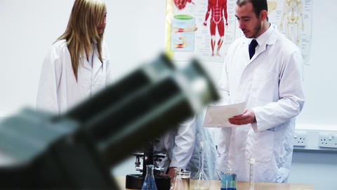Man in lab coat looking into a microsope Stock Video Footage