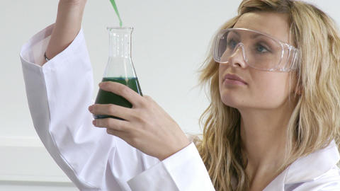 Woman looking at chemicals Stock Video Footage