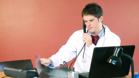 Attractive doctor on phone examining an xray in ho Footage