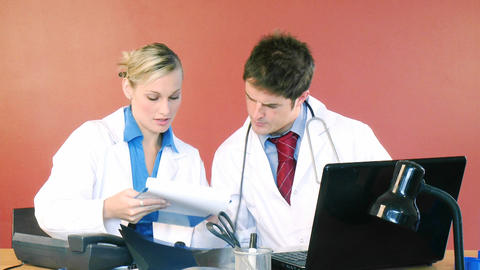Doctors studying a patient report Stock Video Footage