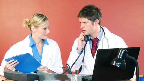Doctors working in office and talking on phone Footage