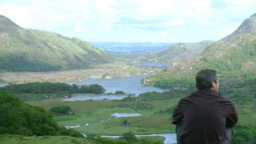 Man sitting on the top of a mountain enjoying the landscape Stock Video Footage