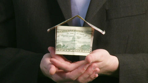 Businessman holding house of Dollars Stock Video Footage