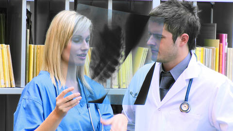 Female and male doctors examining an xray in hospi Footage