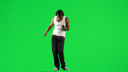Ethnic boy with a headset on dancing music against green screen Footage