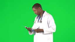 AfroAmerican doctor writing notes against green sc Footage