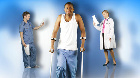 Ethnic young man walking with crutches with doctors in the background footage Footage