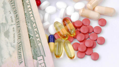 Dollars and colourful pills turning Stock Video Footage