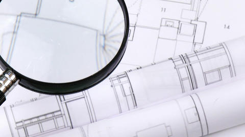 High view of magnifying glass over architecture pl Stock Video Footage