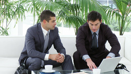 Businessmen sitting on sofa using a laptop Footage