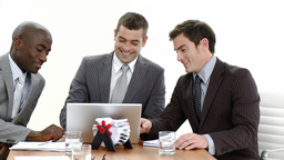 Three businessmen in a meeting using a laptop Footage