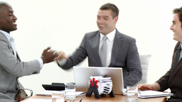 Close up of businessmen in a meeting using a laptop and talking on phone Footage