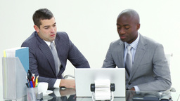 Two businessmen working with a laptop in office Stock Video Footage