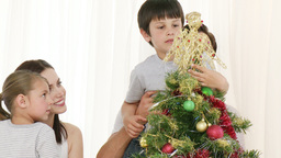 Family decorating a Christmas tree at home Footage