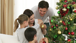 Parents and children decorating a Christmas tree Footage
