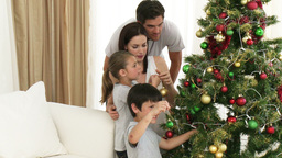 Young family decorating a Christmas tree together Footage