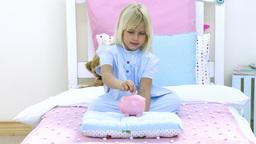 Little girl saving money in a piggy bank Footage