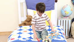 Little boy playing with a train in his bedroom Footage