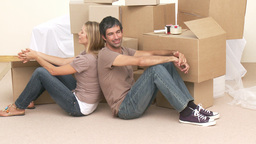 Tired couple sitting on floor after buying house Stock Video Footage