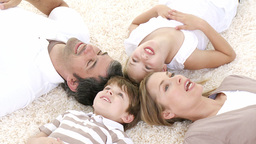 Family lying on floor with heads together Stock Video Footage