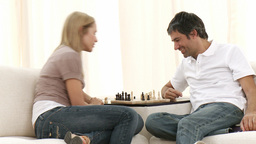 Woman and man playing chess on sofa in livingroom Footage