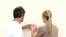 Couple choosing colours to paint new house Stock Video Footage