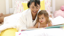 Mother reading a book to her little daughter in be Footage