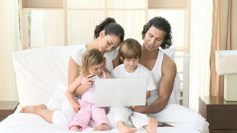 Family in bed using a laptop Stock Video Footage