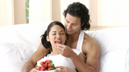 Happy couple sitting in bed eating strawberries Footage