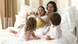 Happy parents and children having breakfast in bed Footage