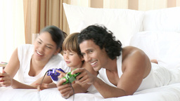 Parents and son playing video games in bed Stock Video Footage