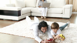 Father and son playing video games and mother using a laptop Footage