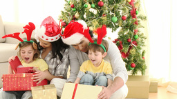 Parents and children opening Christmas gifts at ho Stock Video Footage