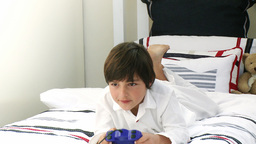 Boy on his bed playing video games Stock Video Footage